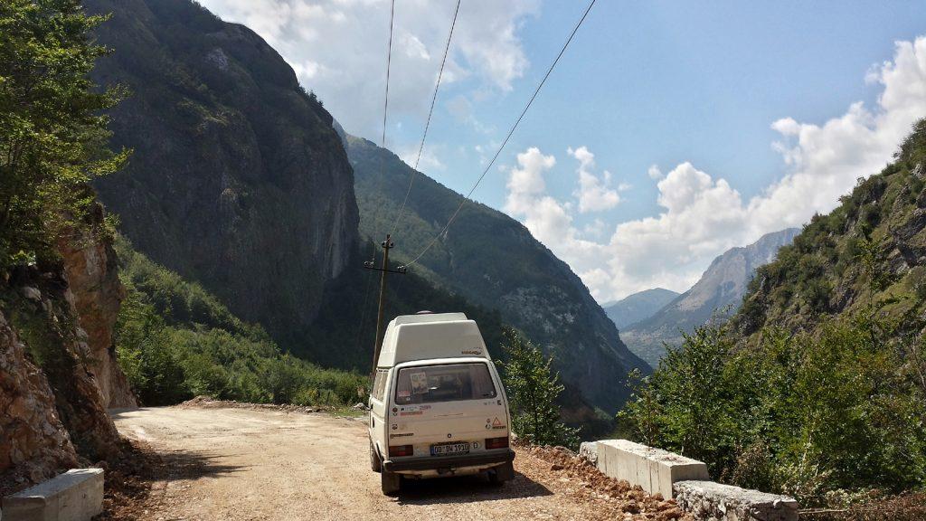 VW Bus Bulli auf Schotterstraße in Albanien im Kelmend
