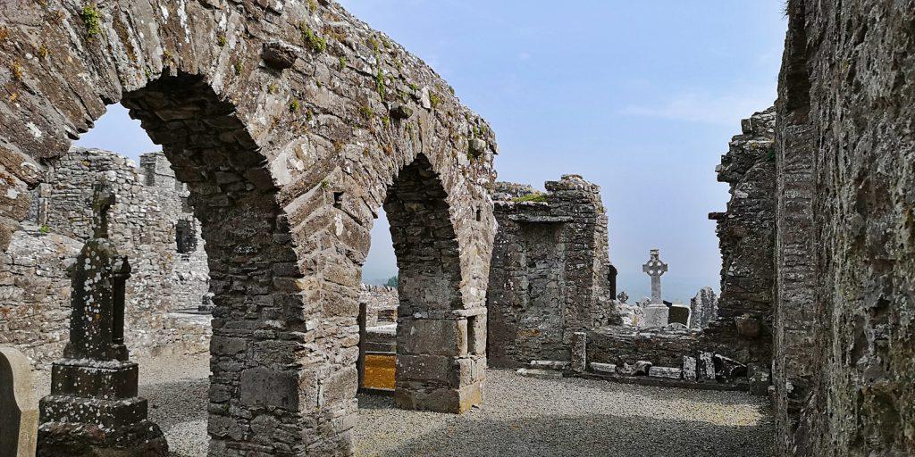 Ruinen auf dem Hill of Slane mit Keltenreuz im Hintergrund