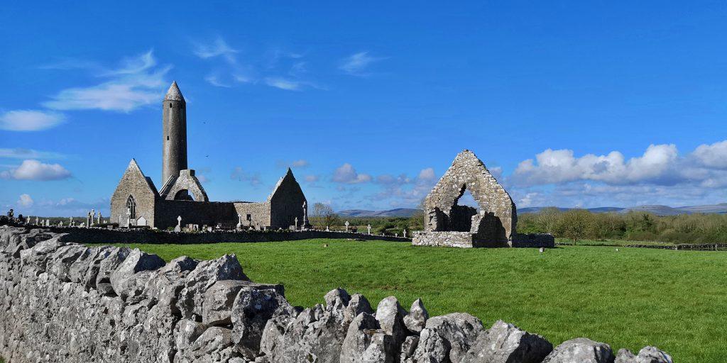 Kilmacduagh mit Rundturm und Kathedrale, im Vordergrund die Kirche von St. John the Baptist